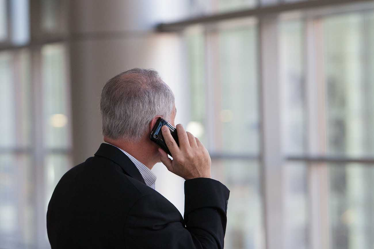 Grey haired man in suit talking on a phone in the office