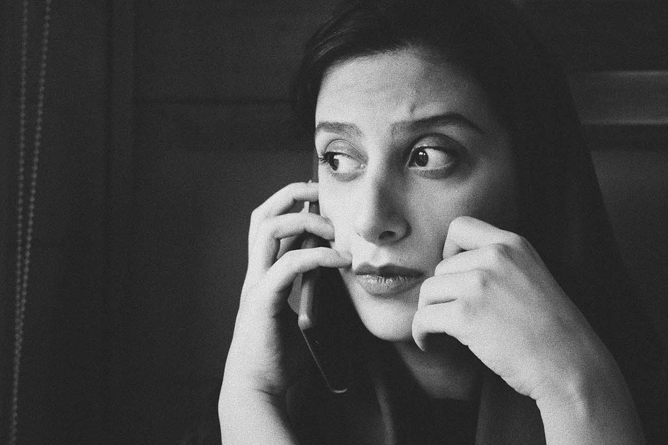 Black and white photo of upset woman talking on a cell phone