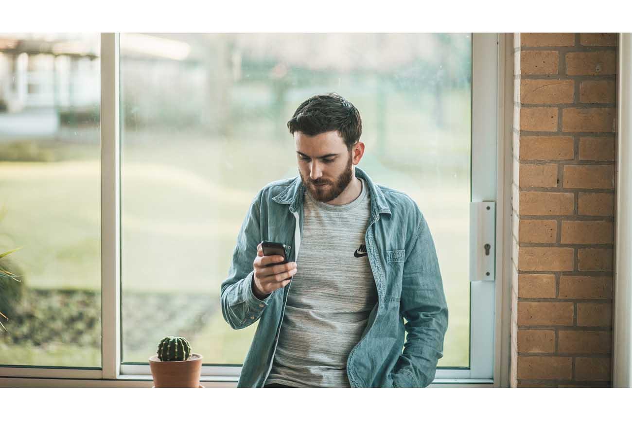 bearded man holding phone