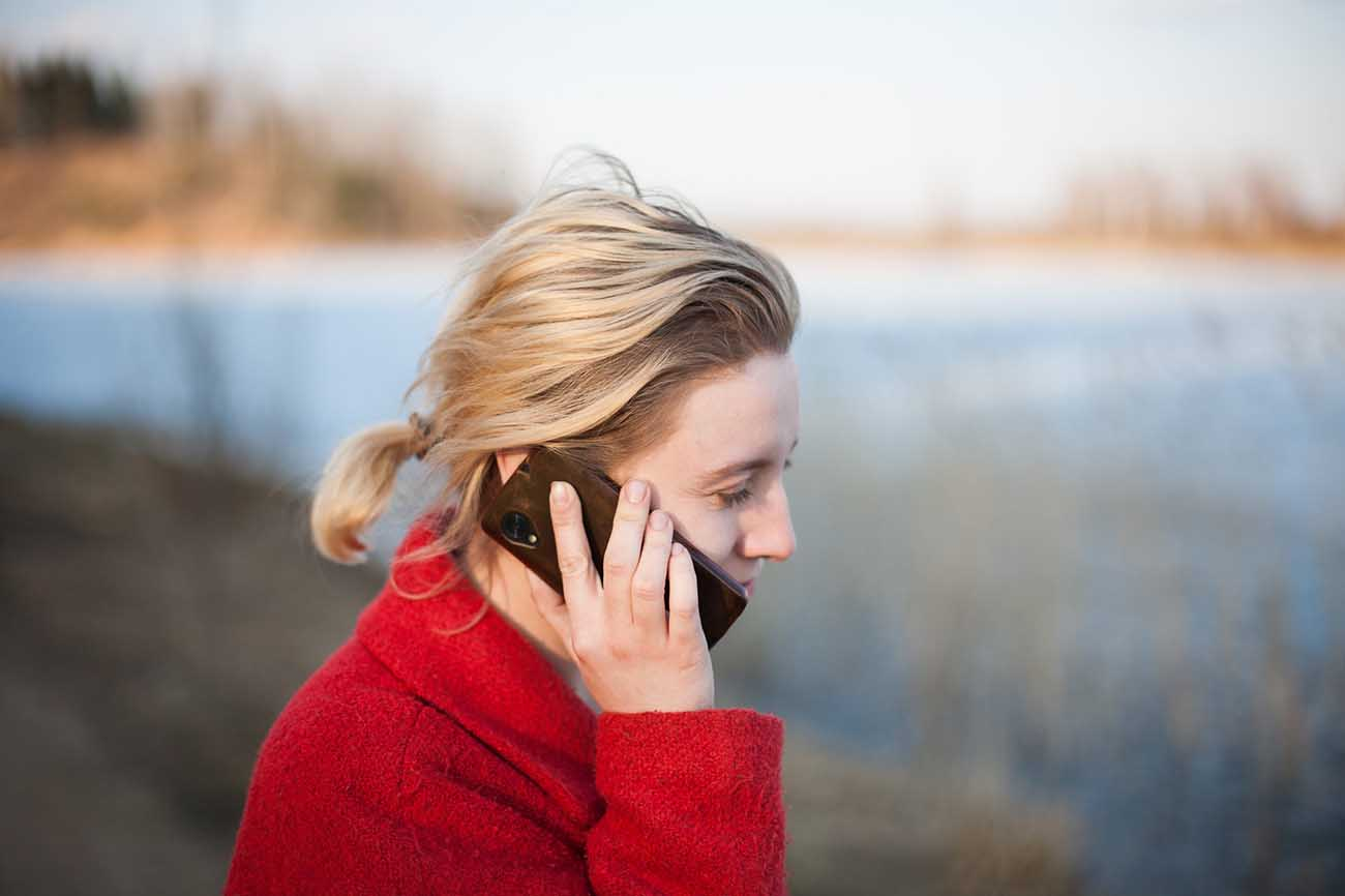 Blonde woman in red sweater talking on a cell phone outside